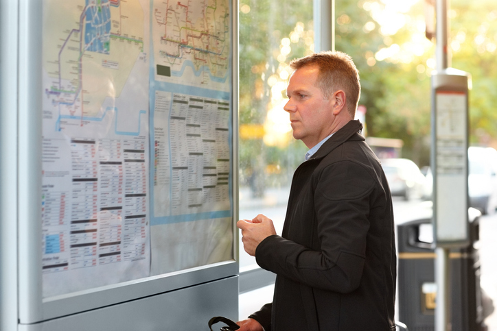 Man at the bus stop checking timetable